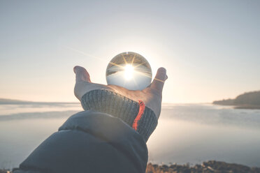 A man holding a reflective sphere in the bright sun - INGF00448