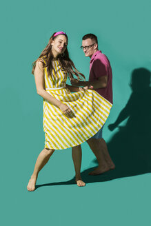 Portrait carefree couple dancing against turquoise background - FSIF03177