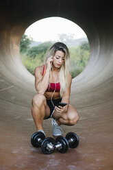 Athletic woman crouching inside a tube with dumbbells and earphones looking at cell phone - FMGF00037
