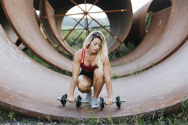 Athletic woman doing weight workout at industrial site - FMGF00043
