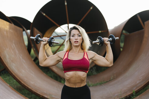 Athletic woman doing weight workout at industrial site - FMGF00052