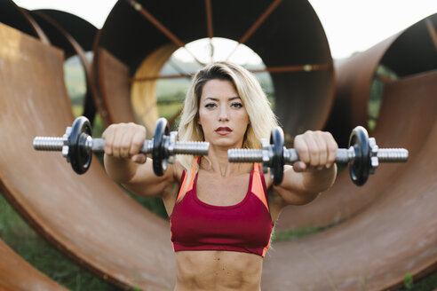 Athletic woman doing weight workout at industrial site - FMGF00055