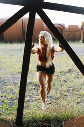 Athletic woman doing stretching exercise at industrial site - FMGF00061