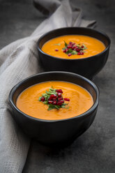 Bowl of carrot ginger coconut soup with topping of parsley and pomegranate seed - LVF07454