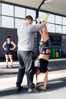 Man in gym helping friend do handstand - CUF45170