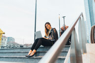Businesswoman, sitting outdoors on steps, using laptop, luggage beside her, low angle view - CUF45200