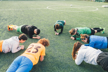 Football players in plank position on pitch - CUF45239