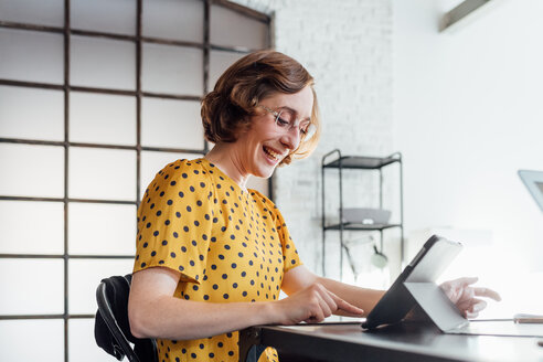 Businesswoman using digital tablet smiling - CUF45269