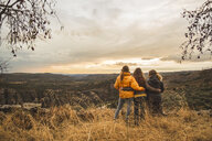 Spain, Alquezar, three friends embracing on a hill overlooking the scenery - AFVF01625