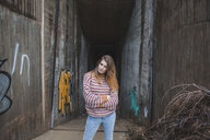 Portrait of young woman standing at graffiti underpass - AFVF01631