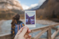 Spain, hand holding instant photo of a woman on a bridge in Ordesa National Park - AFVF01637