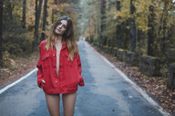 Portrait of young woman standing on country road wearing red jacket - AFVF01646