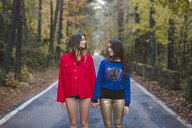Two young women standing on country road facing each other - AFVF01649