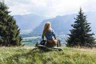 Germany, Bavaria, Oberammergau, young woman hiking sitting on bench on mountain meadow - TCF05836