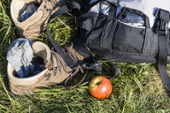 Hiking boots, backpack and apple on a meadow - TCF05845