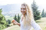 Germany, Bavaria, Oberammergau, portrait of smiling young woman eating an apple on mountain meadow - TCF05848