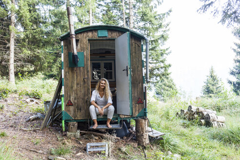 Germany, Bavaria, Oberammergau, smiling young woman sitting in trailer on mountain meadow - TCF05854