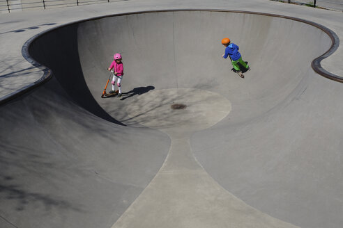 Brother and sister on scooters playing at sunny skate park - FSIF03224