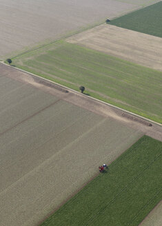 Aerial view tractor in sunny agricultural crop, Hohenheim, Baden-Wuerttemberg, Germany - FSIF03251