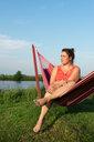 Woman relaxing in hammock by river, Broek, Friesland, Netherlands - CUF45355