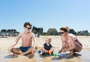 Parents playing with toddler on beach - CUF45385