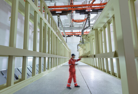 Worker inspecting painted chassis in drying room in trailer factory - CUF45466
