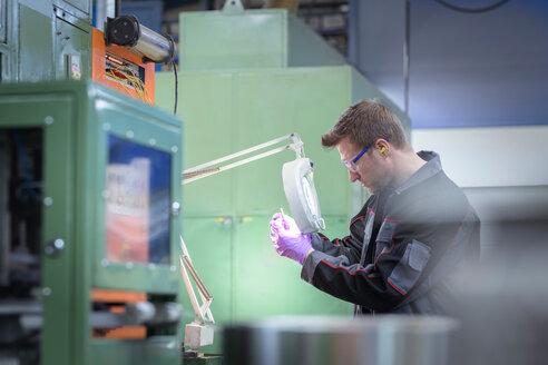 Engineer inspecting pressed metal part in metal pressing factory - CUF45502