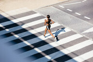 Young woman running on zebra crossing - CUF45661