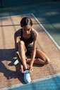 Young woman tying shoelace in sports court - CUF45667