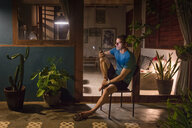 Mature man sitting on patio at night looking at smartphone - CUF45739