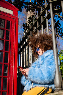 Woman by traditional red telephone box texting on smartphone - CUF45787