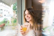 Woman having drink by window in restaurant - CUF45874