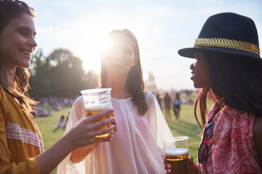 Three young female friends with glasses of beer at Holi Festival - CUF45952