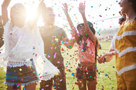 Five young adult friends throwing confetti at Holi Festival - CUF45955