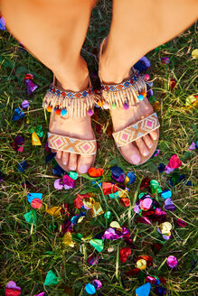 Overhead view of young woman standing amongst confetti on grass at Holi Festival, detail of feet - CUF45958