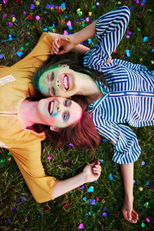 Two young women covered in coloured chalk powder lying on grass at Holi Festival, overhead portrait - CUF45976
