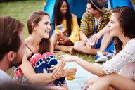 Friends sitting and enjoying music festival - CUF46015