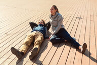 Couple relaxing on wooden decking - CUF46048