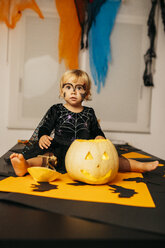 Portrait of little girl with painted face and fancy dress sitting on table with Jack O'Lantern - JRFF01878