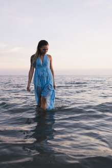 Young woman wearing blue dress walking in water at seashore  by sunset - MAUF01720