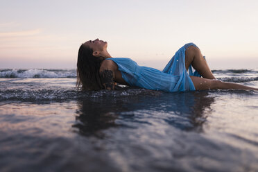Young tattooed woman wearing blue dress lying in water at seashore by sunset - MAUF01723