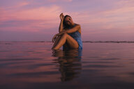 Profile of young woman sitting in the water at seashore by sunset - MAUF01726