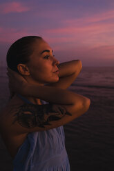 Profile of young woman with tattoo in front of the sea by sunset - MAUF01729