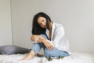 Portrait of attractive young woman sitting on bed with white rose - AFVF01661