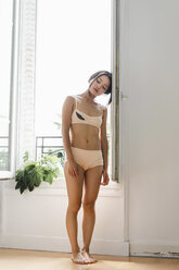 Attractive young woman in lingerie standing at the window - AFVF01673