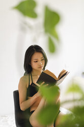 Attractive young woman in lingerie sitting on chair at home reading book - AFVF01679