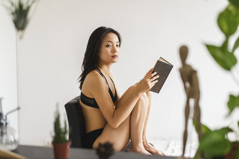 Portrait of attractive young woman in lingerie sitting on chair at home reading book - AFVF01682