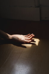 Woman's hand on the floor in sunlight - AFVF01685