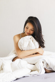 Smiling young woman sitting in bed - AFVF01691