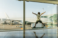 Spain, Barcelona airport, Boy in departure area, jumping in front of glass pane - JRFF01906